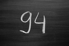 Number ninety four enumeration written with a chalk on the blackboard Royalty Free Stock Image