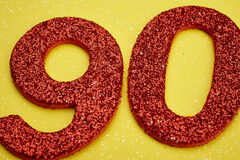 Number ninety red color over a yellow background. Anniversary Stock Image