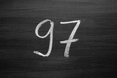 Number ninety seven enumeration written with a chalk on the blackboard Royalty Free Stock Photos