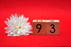 Number ninety three with a white daisy. On a red background stock photography