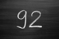 Number ninety two enumeration written with a chalk on the blackboard Royalty Free Stock Image