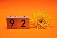 Number ninety two with a yellow daisy. On an orange background royalty free stock photo