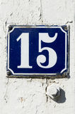 Number 15. Old enameled house sign with number fifteen on white wooden wall with color flakes. Nykoping, sweden stock image
