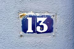 Number 13. Old house number thirteen 13 embeded in a blue plastered wall Stock Images