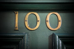 Number one hundred brass door number on weathered painted doorway Royalty Free Stock Image