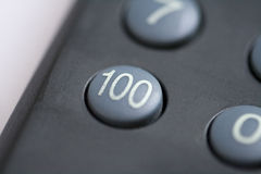 Number one hundred button. A close up of a number one hundred button on a remote control stock photo