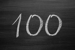 Number one hundred enumeration written with a chalk on the blackboard Stock Photos