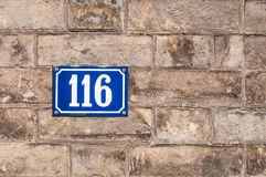Number one hundred and sixteen painted on metal plate on brick w Royalty Free Stock Photography