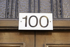 Number one hundred on a wall. Detail of a number of information in a house in the city Stock Photo