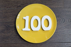 The number one hundred on the yellow plate. Royalty Free Stock Image