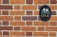 Number one plate on brick wall Stock Photo