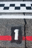 Number one pole position on speedway starting track. Number one pole position sign on speedway starting track with red line and damaged old asphalt royalty free stock photography