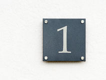 Number one sign. Sign attached to a white wall with the number one on it Royalty Free Stock Image