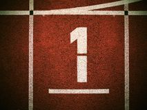 Number one. White track number on red rubber racetrack, texture of running racetracks in small outdoor stadium Royalty Free Stock Image