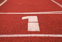 Number one. White track number on red rubber racetrack, texture of running racetracks in stadium Royalty Free Stock Image