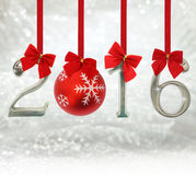 2016 number ornaments hanging on red ribbons. In a glittery background Royalty Free Stock Photo