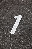The number 1 painted on the tarmac. The number one painted on the tarmac of the road stock photo