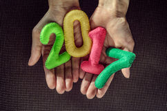 Number 2017 in the palms. New Year concept. Multi-colored figures of felt in the palms. Toy felt symbols. 2017 Stock Photo
