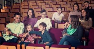 Number of people enjoying film screening and popcorn Stock Photos