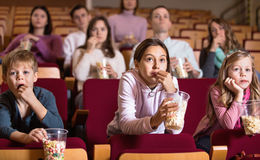 Number of people enjoying film screening and popcorn Royalty Free Stock Photography