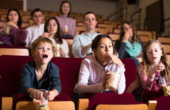 Number of people enjoying film screening and popcorn Royalty Free Stock Photos