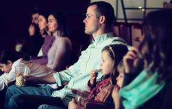 Number of people enjoying film screening and popcorn Stock Image