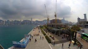 A number of people walking along Tsim Sha Tsui Promenade time-lapse stock video footage