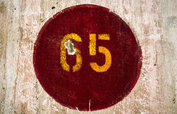 Number 65 painted in a wall of an old train station Royalty Free Stock Images