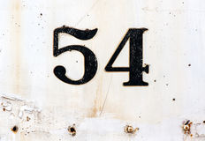 Number 54 plated on rusty white painted surface Royalty Free Stock Image