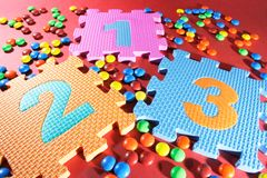 Number Puzzles and Chocolate Lollies. On Red Background Stock Photo