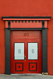 Number 20 Red Double Door. Street number 20 over red double doors with the letter B on each door framed by black and red arch and columns stock images