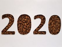 Number 2020 with roasted coffee beans and white background, design for new year celebration. Lot of coffee beans toasted, ingredient for drinks with caffeine royalty free stock photography