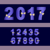 2017 number set with gold ribbon in blue dark background. Shiny gold number set with blue holes motive and gold ribbon .This new number style is good for Stock Photography