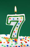 Number seven birthday candle. On green background Royalty Free Stock Photos