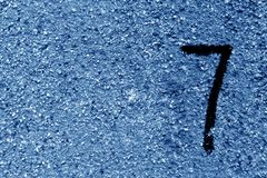 Number seven on blue grungy cement wall. Signs and symbols Stock Photos