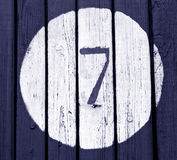 Number seven on blue toned wooden wall Stock Image