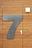Number seven on door. Door made from planks with large metal house number seven Royalty Free Stock Image