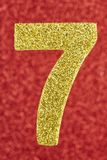 Number seven golden color over a red background. Anniversary. Vertical Stock Illustration