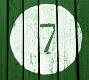 Number seven on green toned wooden wall. Numbers and figures Stock Photo