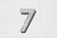 Number seven on old wall. Textured metal number seven on an old white cracked wall Royalty Free Stock Images