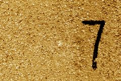 Number seven on orange grungy cement wall. Signs and symbols Royalty Free Stock Images