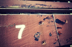 Number seven painted on an old wooden seat. Number seven painted on an old wooden seat, conceptual picture with copy space on the right Royalty Free Stock Images