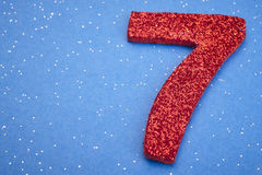 Number seven red color over a blue background. Anniversary Royalty Free Stock Image