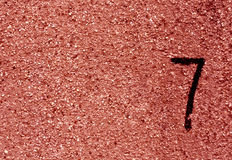 Number seven on red grunge wall surface. Royalty Free Stock Image