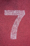 Number seven on running track. White track number on red rubber racetrack Stock Image