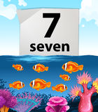 Number seven with seven fish swimming in the sea Stock Images