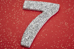 Number seven silver color over a red background. Anniversary Royalty Free Stock Images