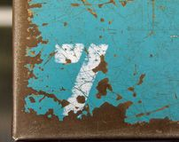 Number seven stenciled on old tool box lid. Number seven stencil in white paint on scratched and chipped old teal metal surface Stock Photography