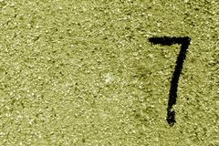 Number seven on yellow grungy cement wall. Signs and symbols Stock Image