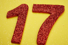 Number seventeen red color over a yellow background. Anniversary Stock Photo